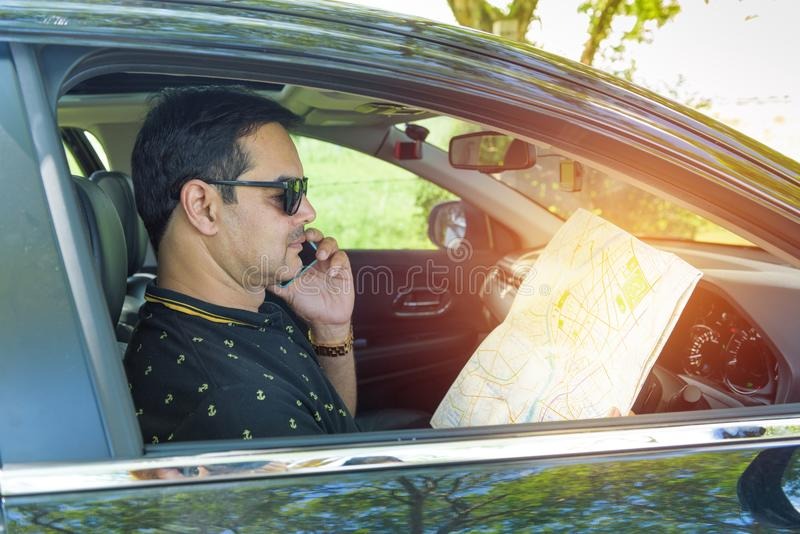 Man in casual dress use smart phone and look into the map. While sitting in car stock image