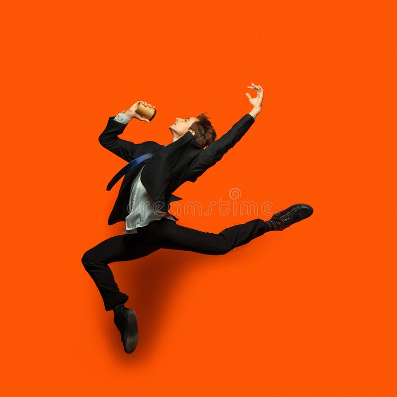 Man in casual office style clothes jumping isolated on studio background. Man in casual office style clothes jumping and dancing isolated on bright orange stock images