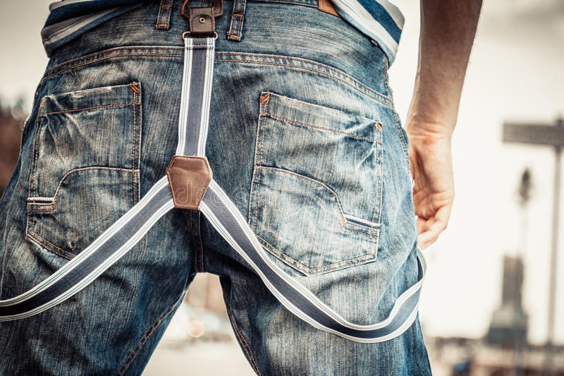 Man casual style denim pants and suspenders. Fashion. closeup young fashionable man casual style wearing denim pants with suspenders back view outdoor stock image