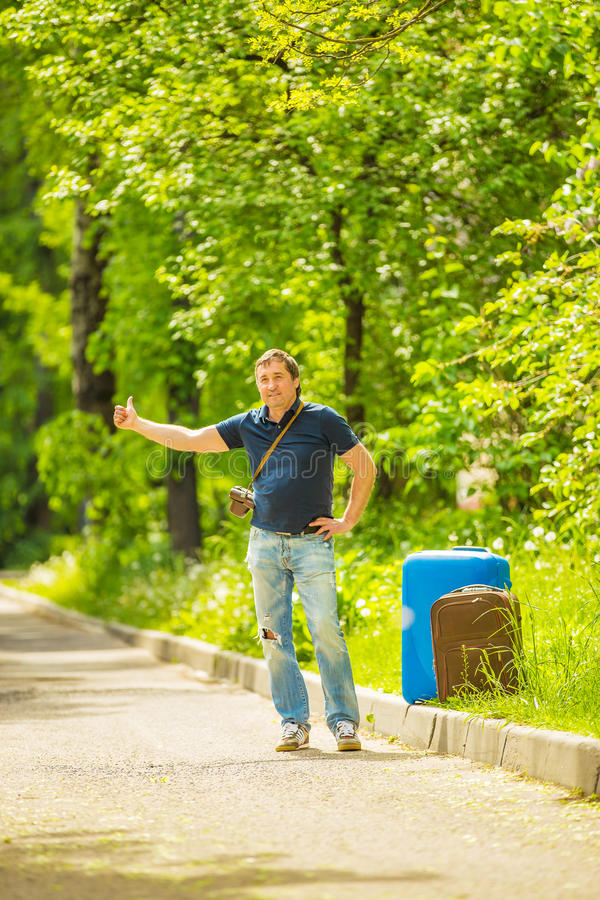 A man catches a passing car. On a Sunny day royalty free stock photography