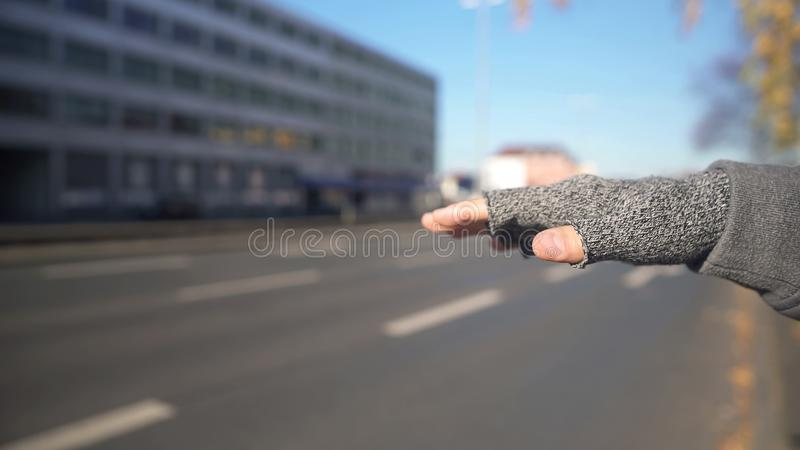 Man catching car, cheap way of travelling, unsafe journey risk, hand close up. Stock photo royalty free stock photo