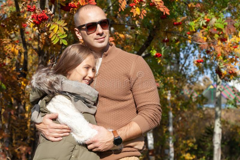 Man caucasian dad in sunglasses hugs beautiful daughter on background of colorful autumn trees. Concept family weekend royalty free stock photo