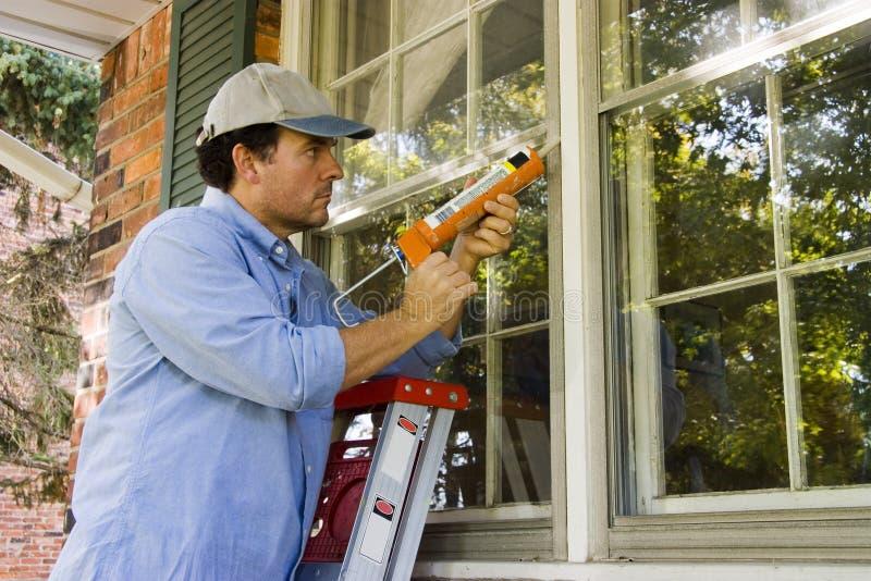 Man Caulking Window royalty free stock photo