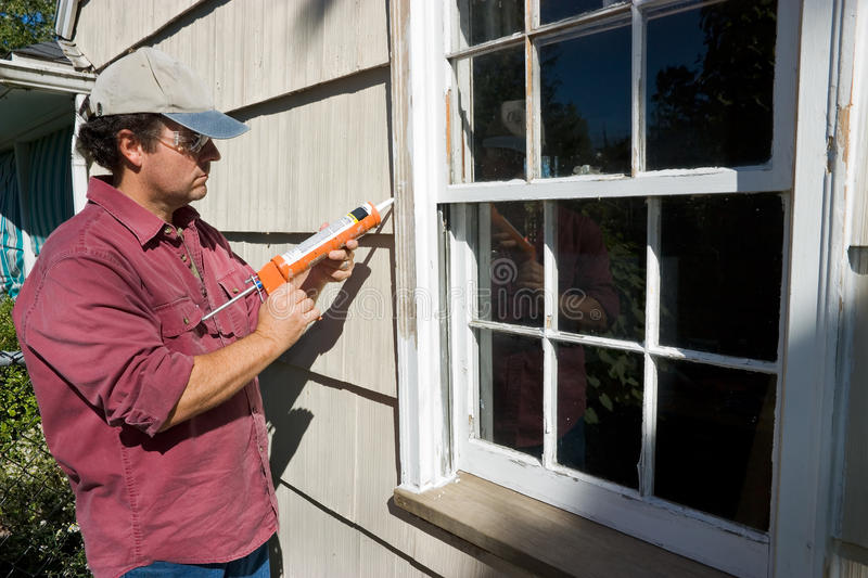 Man Caulking Window. A Man Caulking And Fixing An Outside Window To Insulate Against the Winter Weather royalty free stock images