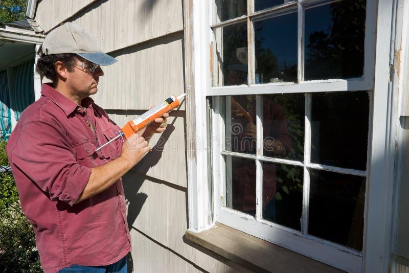 Man Caulking Window royalty free stock images