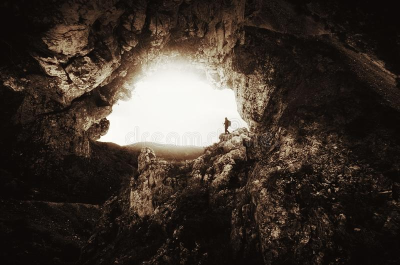 Man at cave entrance with giant cliffs. Man in cave. Mysterious dark cave with man. Explorer in underground cave. Speleology in cave royalty free stock photo