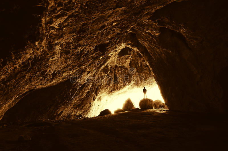 Man at cave entrance royalty free stock photo