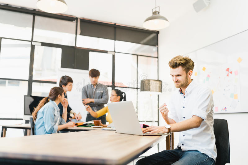 Man celebrate success pose with multi-ethnic diverse team meeting at office. Creative group, business coworker, or college student stock photography
