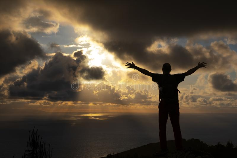 Man celebrating victory at the background the sky with clouds at sunset royalty free stock photos