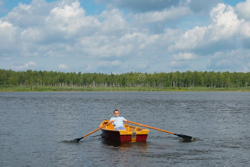 A man, in the center of the lake, is swimming in a boat with oars, against the background of a beautiful landscape stock photos