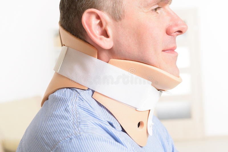 Man in cervical collar. Man with a surgical cervical collar suffering from neck pain royalty free stock photo