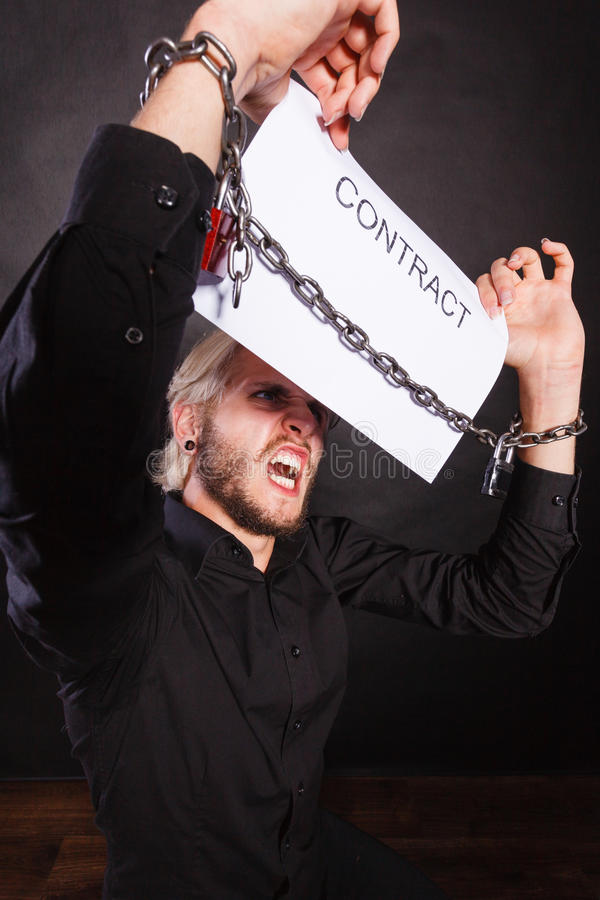 Man with chained hands holding contract stock image