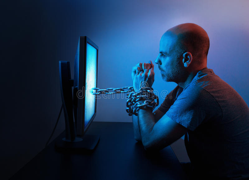 Man chained to computer. A man is chained to computer late at night