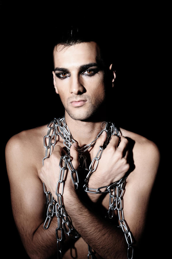 Man In Chains. Handsome, androgynous male model in chains royalty free stock images