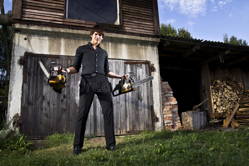 Man with chainsaw. Dangerous man with chainsaw in the evening royalty free stock images