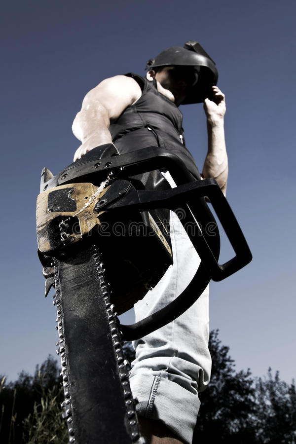 Man with chainsaw. Dangerous man with chainsaw and in the mask royalty free stock images
