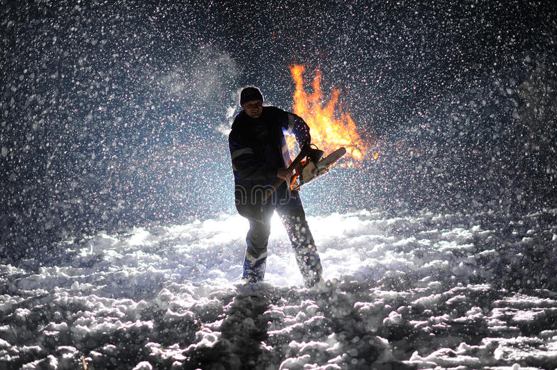 Man with chainsaw in the hands. On the night snow background stock photography