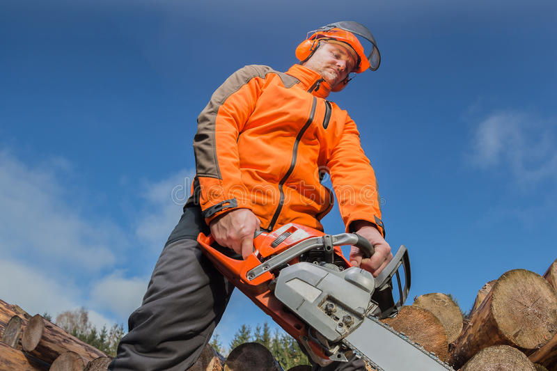 Man with chainsaw. A man with a chainsaw outdoor stock photography
