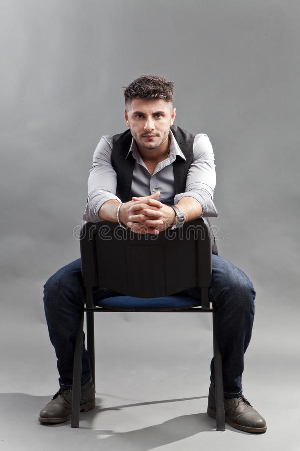 Man on chair. Pensive young man in stress, sitting on chair and looking straight royalty free stock photography