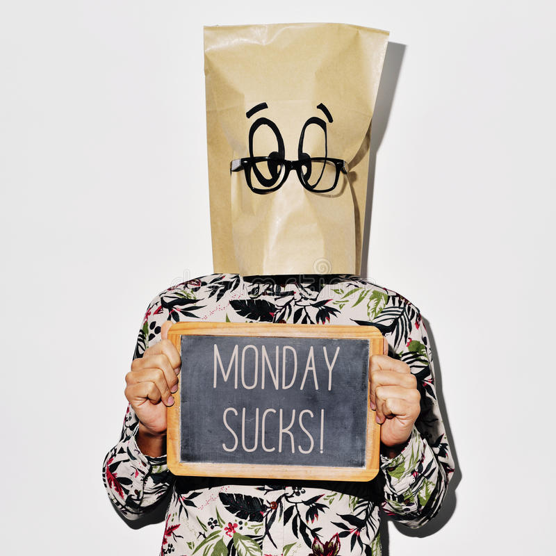 Man with a chalkboard with the text monday sucks. A young caucasian man with a paper bag with a funky face in his head shows a chalkboard with the text monday stock photo