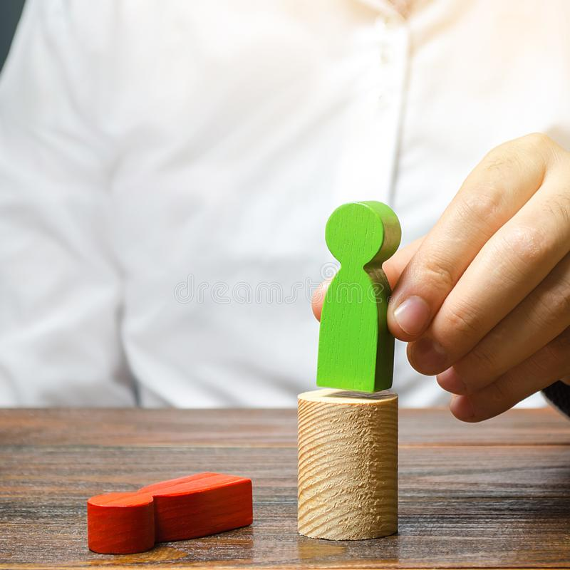 The man changed the red figure to the green one at the post. firing staff. Head Offset. Business optimization, replacement of key. Employees with loyal ones royalty free stock image