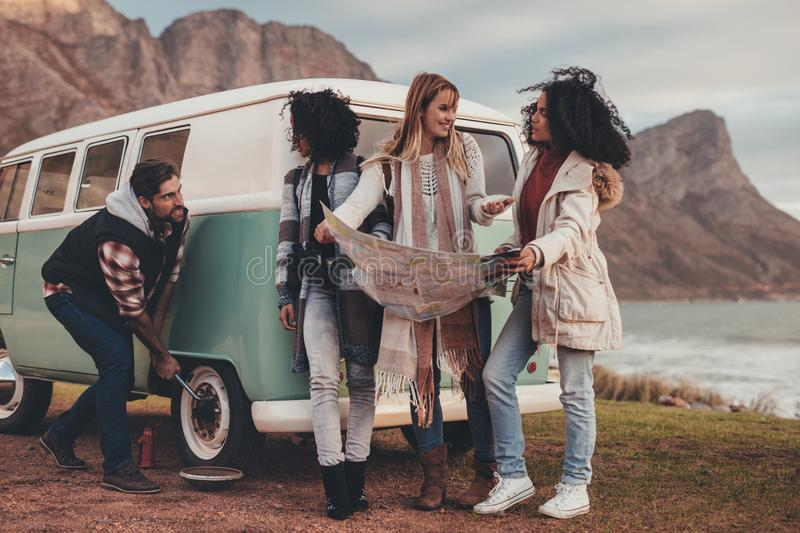 Man changes flat tire with friends standing by. Friends on a road trip. Man changing the punctured wheel of van on the road while women checking the route map stock photography