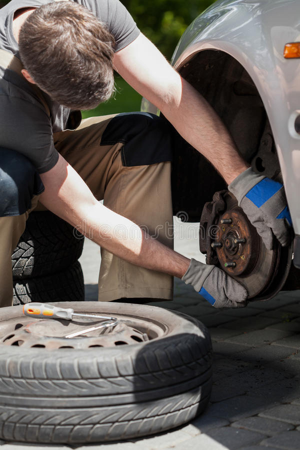 Man changing a car brakes. Close-up of a man changing a car brakes royalty free stock image