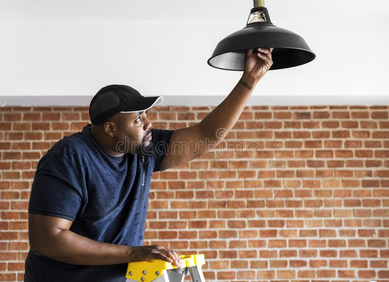 Man changing lightbulb in the house service royalty free stock images