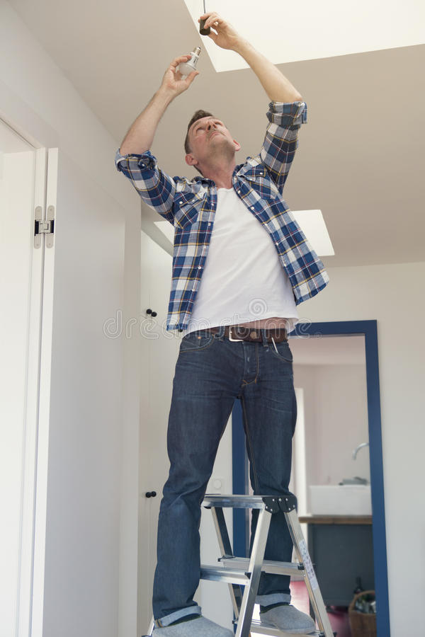 Man changing a lightbulb in living room royalty free stock photos