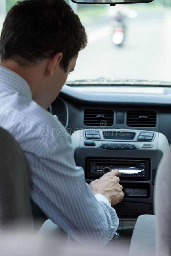 Man changing song in car stock photography
