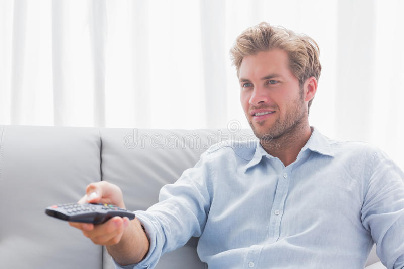 Download Man Changing Tv Channel Sat On The Couch Stock Photo - Image: 31802006