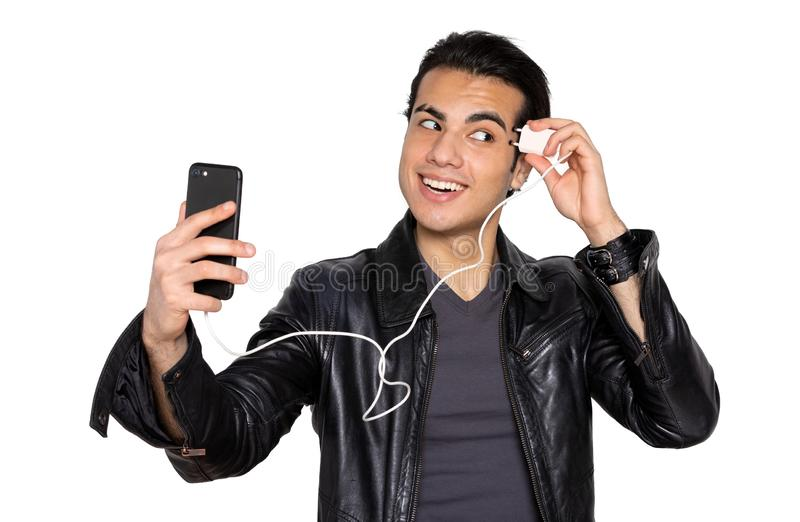 Man charges the phone head on an isolated. A young man in a black leather jacket charges your cell phone from the head on an isolated background. the concept of stock photography