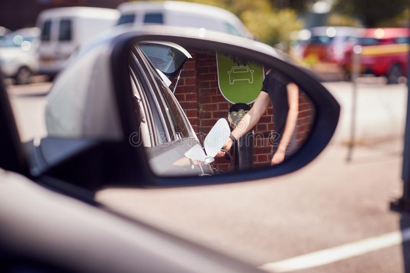 Man Charging Electric Vehicle Reflected In Car Side Mirror stock photography