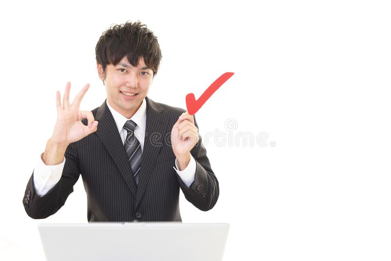 Man with a check mark. Smiling Asian businessman using a laptop stock photos