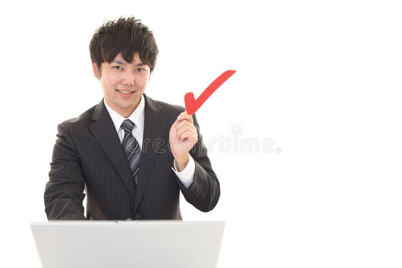 Man with a check mark. Smiling Asian businessman using a laptop stock photo