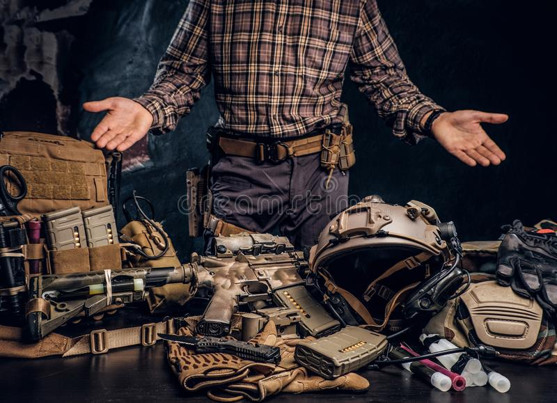Man in a checkered shirt showing his military uniform and equipment. Modern special forces equipment. Studio photo royalty free stock photos