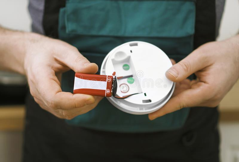Smoke detector. Man checking battery in smoke detector in the kitchen royalty free stock images