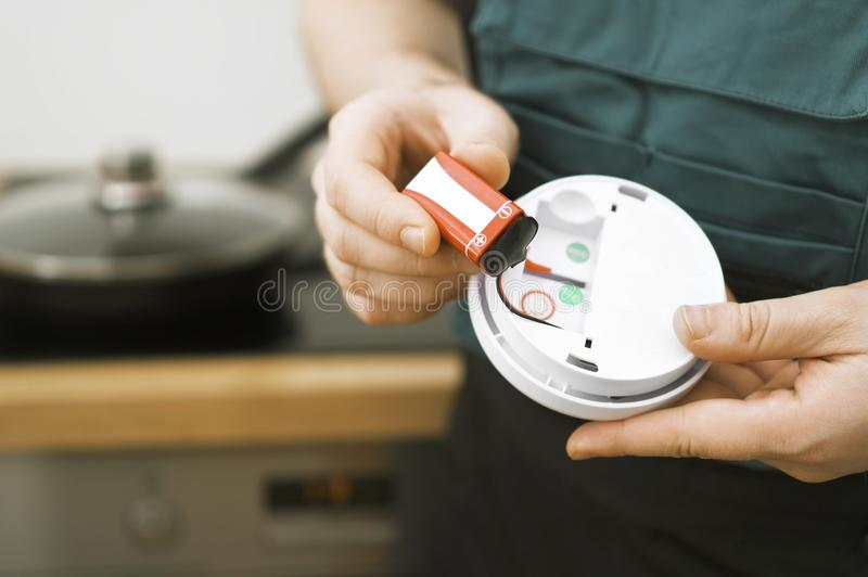Smoke detector. Man checking battery in smoke detector in the kitchen stock photo