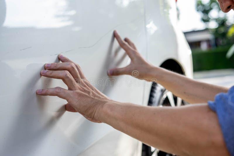 Man checking car scratch dent damage. royalty free stock image
