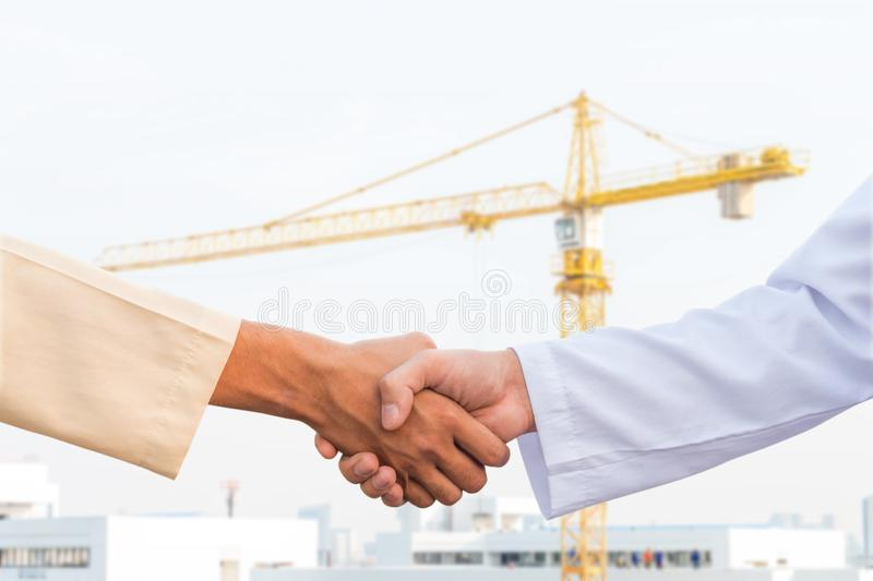 The man checking the hand with commitment to sucess at construction site and crane background.  stock photography