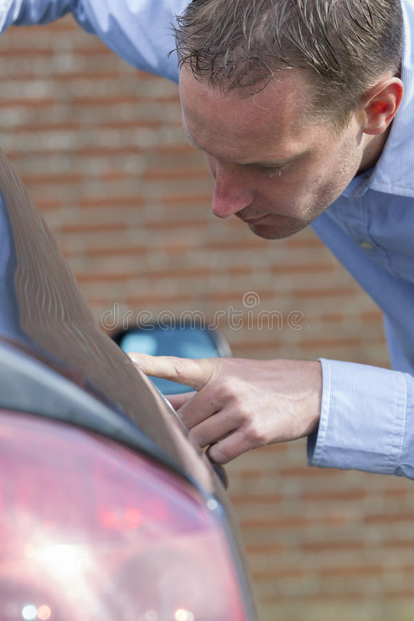 Man Checking His Car. Mid adult man checking his car for scratches and dents. Vertical shot royalty free stock photos