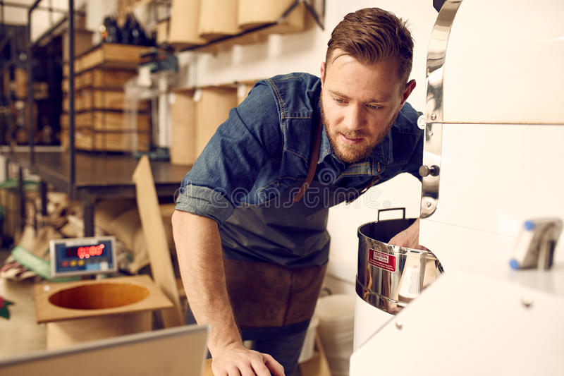 Man checking his laptop while operating a modern coffee roaster. Young man working in a coffee bean roastery and cehcking his laptop while working with a modern stock images