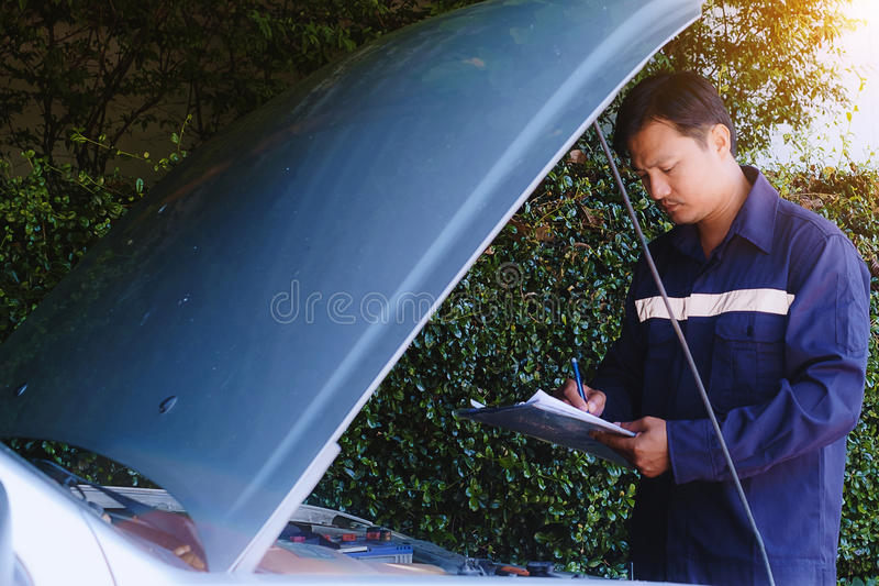 Man checking the list of items to repair the car stock image