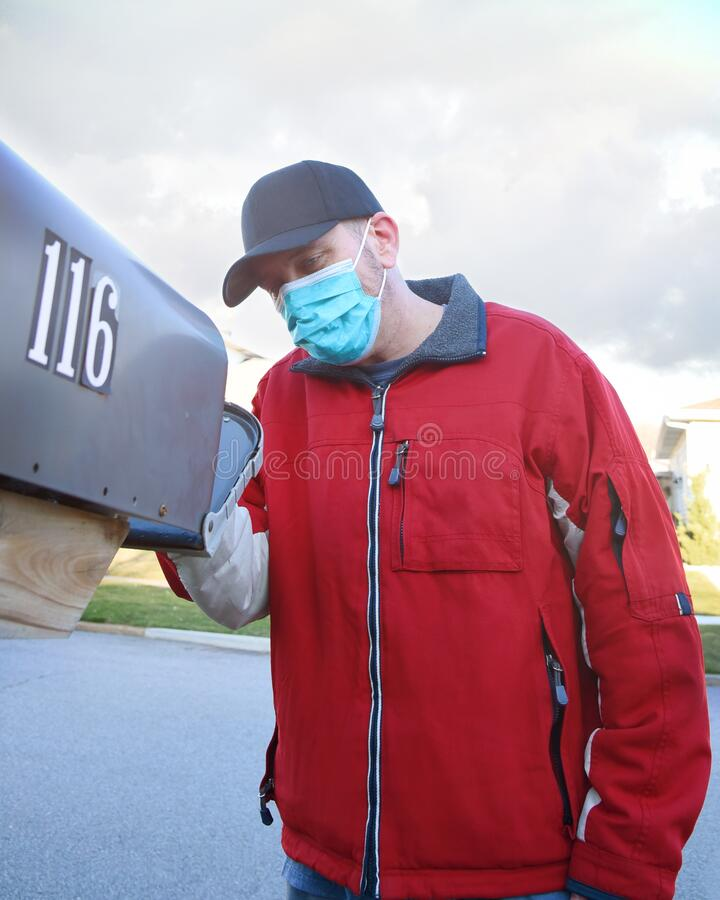 Man Checking Mailbox Wearing a Civid-19 Face Mask royalty free stock image
