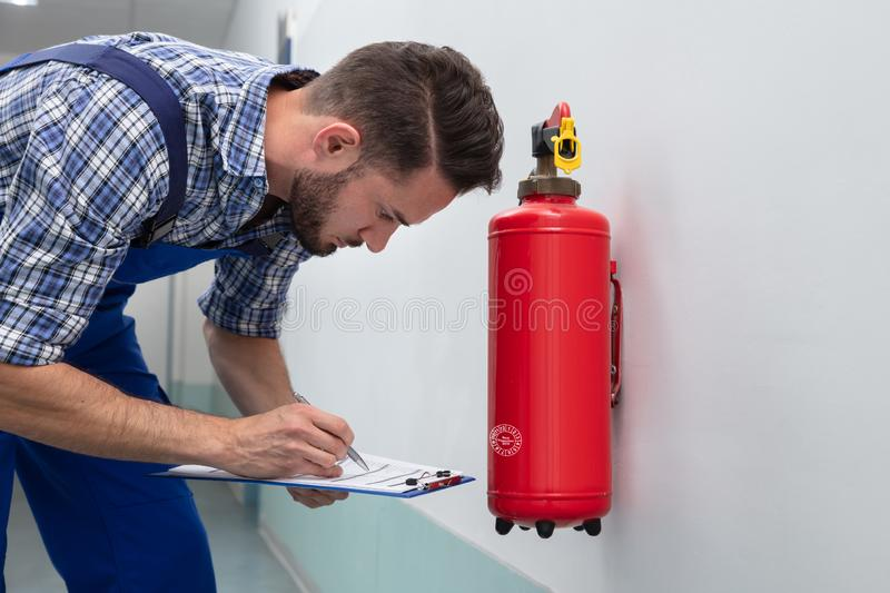 Man Checking Symbol On Fire Extinguisher royalty free stock images