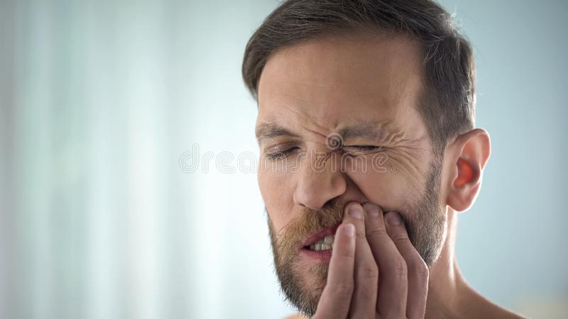 Man checking teeth in front of mirror, dental disease, gum infection, pulpitis royalty free stock photo