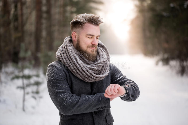 Man checking time in winter woods royalty free stock photography