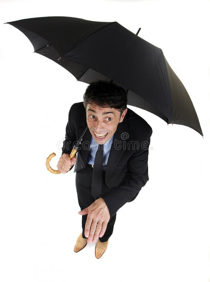 Man checking the weather. Humorous high angle full length portrait of a businessman sheltering under his umbrella checking on the rain holding out his hand to royalty free stock images
