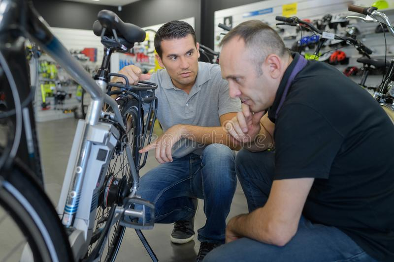 Man checks bike before buying in sports shop. Checking royalty free stock photos