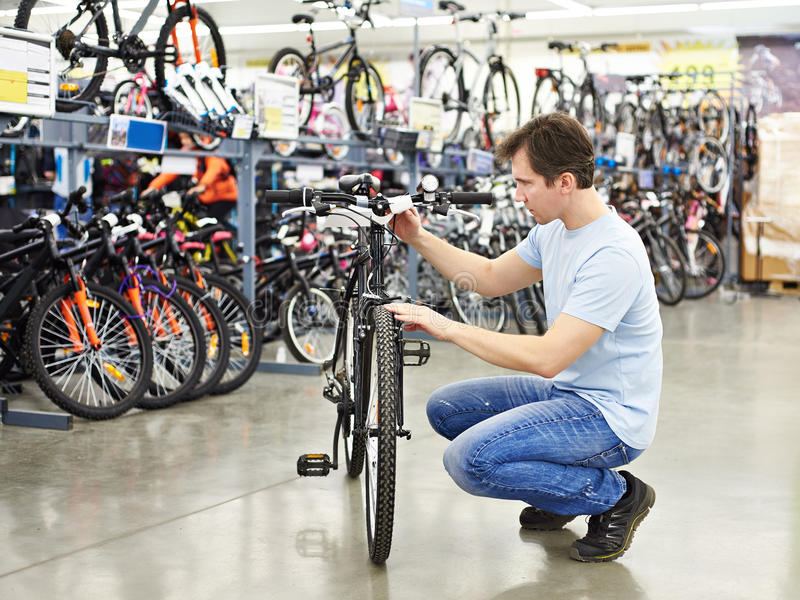 Man checks bike before buying in sports shop. Man checks a bike before buying in the sports shop royalty free stock images